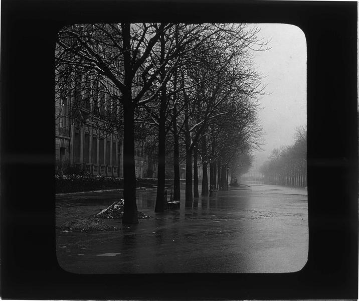 Crue de la Seine : avenue inondée avec hommes circulant en barque en arrière-plan