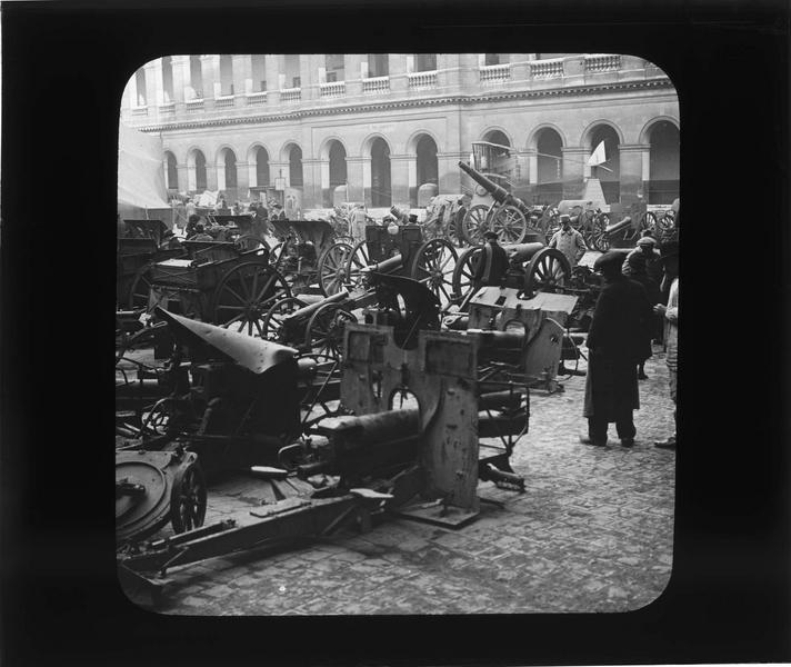 Cour d'honneur, exposition de canons pris aux Allemands (trophées militaires) et biplan Caudron en arrière-plan, vue animée