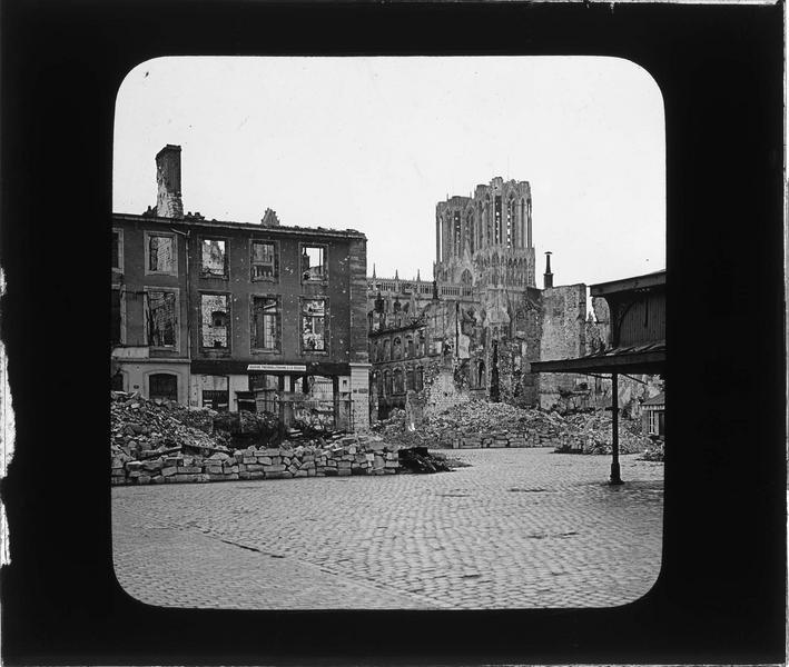 Maisons en ruines bordant la place et tours de la cathédrale en arrière-plan, côté nord