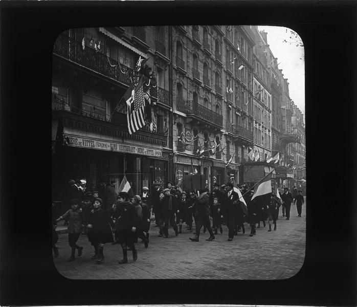 Façades sur rue animée et hommes et enfants marchant drapeaux à la main le jour de la signature de l'armistice