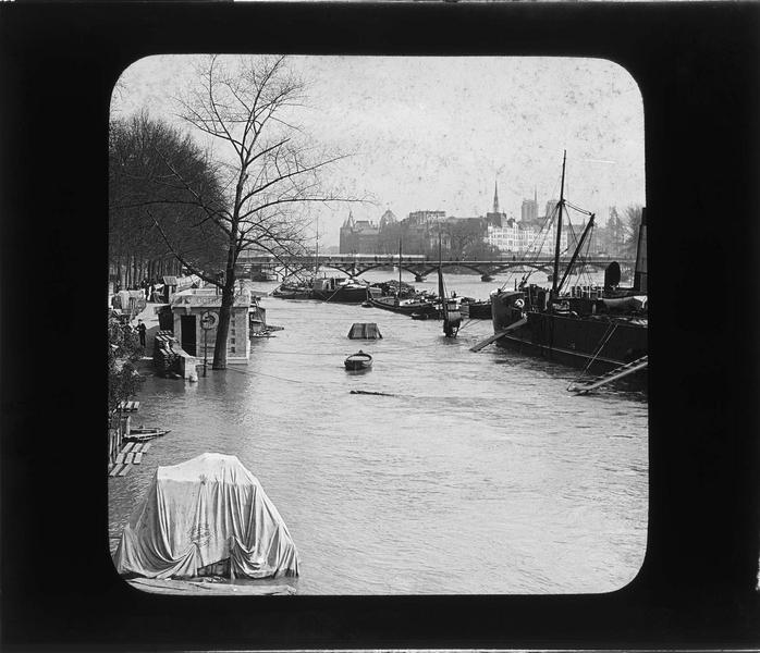 Crue de la Seine : quai inondé, péniches et pont des Arts en arrière-plan depuis le pont du Carrousel