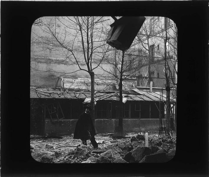 Ruines de l'école bombardée par le raid de gothas allemands depuis la cour et enfant au premier plan