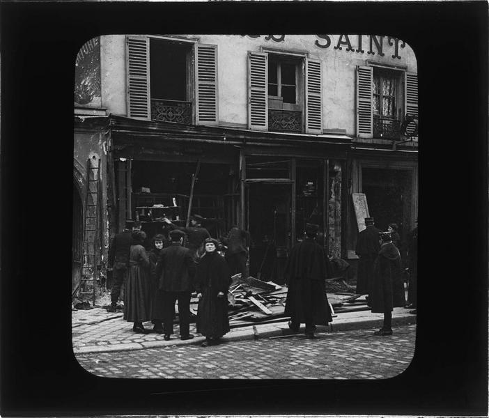 Façade incendiée, vue animée avec passants et policiers constatant les dégâts causés par le raid des bombardiers allemands