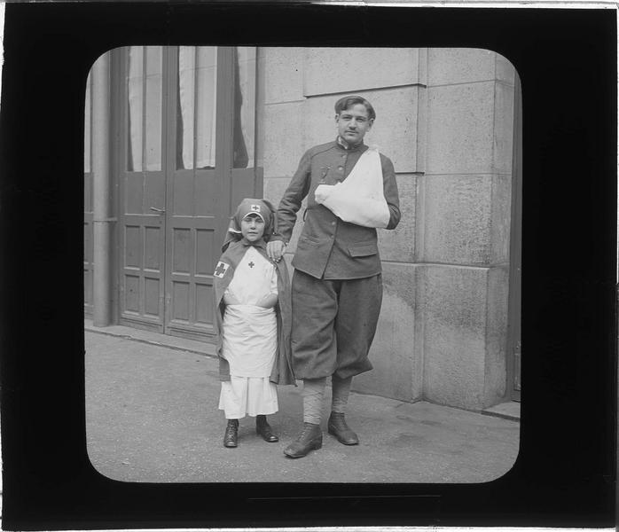 Portrait d'un soldat, bras en écharpe, posant avec une fillette habillée en infirmière