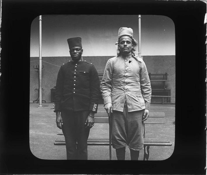 Portrait d'un tirailleur sénégalais et d'un indigène posant dans la cour
