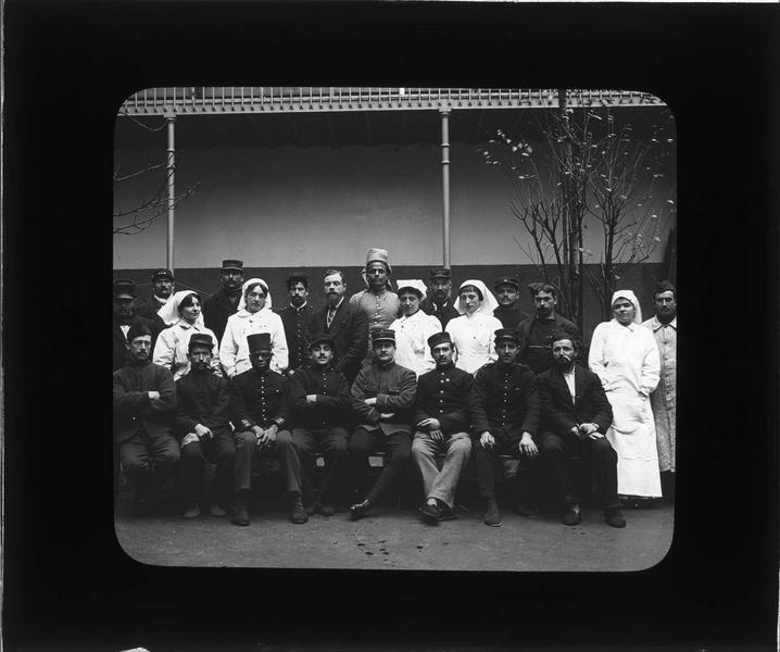 Portrait de groupe : infirmières et soldats posant dans la cour