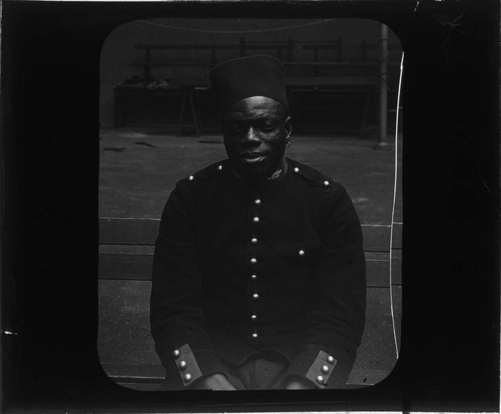 Portrait d'un tirailleur sénégalais posant assis dans la cour