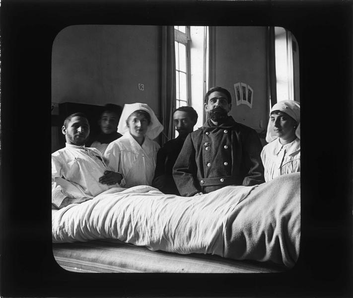 Intérieur : infirmières et soldats autour d'un blessé alité