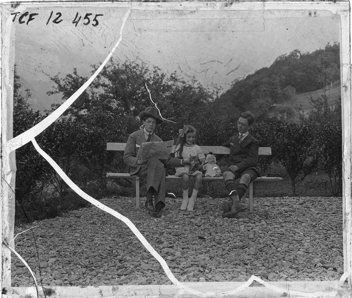 Portrait de deux garçons et une fillette assis sur un banc dans un jardin