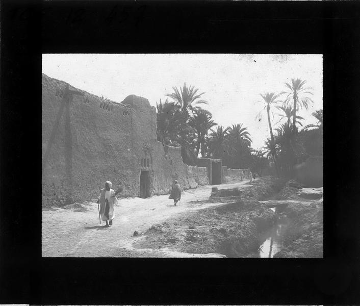 Rue animée du vieux Biskra longée par un ruisseau