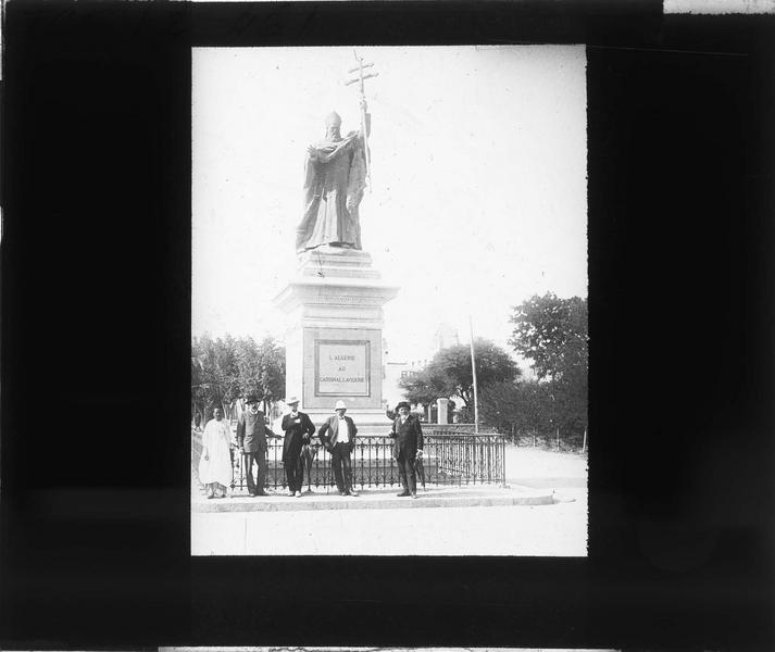 Monument avec cinq hommes posant devant (déplacé en 1962 dans le cimetière chrétien)