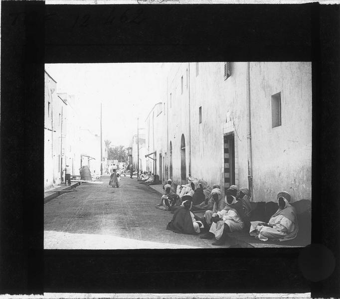 Façades sur rue animée avec hommes en djellaba assis le long du trottoir