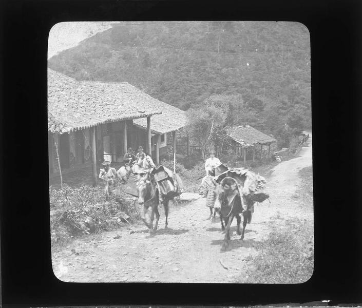 Voyageurs avec chevaux traversant le village
