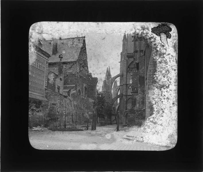 Façade ouest, vue partielle des arcs-boutants côté nord et maisons attenantes avec mur publicitaire Vichy