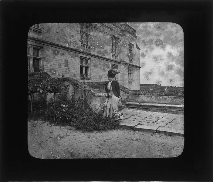 Logis royal, vue partielle de la façade est avec femme appuyée contre la rampe d'escalier donnant sur la terrasse