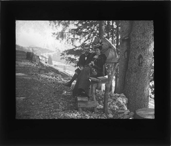 Portrait de A. Bidard et sa fille Hélène assis sur un banc dans la montagne