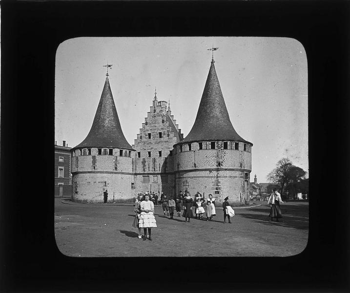 Ecluse de garde fortifiée flanquée de deux tours, façade sur rue animée avec fillettes