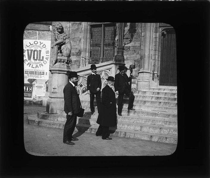 Détail de l'escalier flanqué d'un lion tenant un blason, vue animée avec quatre hommes dont un photographe