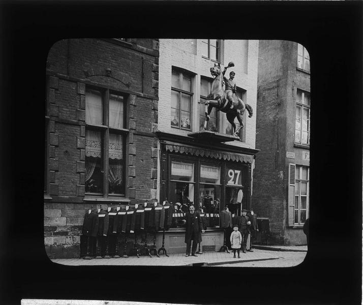 Devanture d'un magasin d'habillement surmontée d'une sculpture de cavalier, vue animée