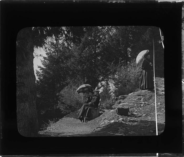 Portrait de Hélène Bidard (à gauche avec l'ombrelle) et deux autres femmes dans la forêt montagneuse