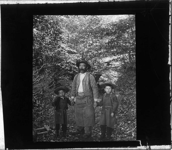 Portrait d'un homme et deux enfants dans un sentier portant des paniers sur le dos