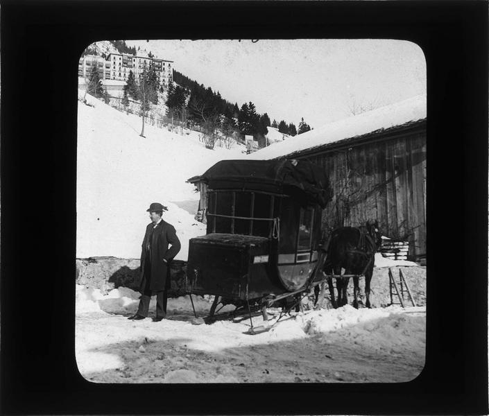 Homme posant à côté d'un traîneau à chevaux