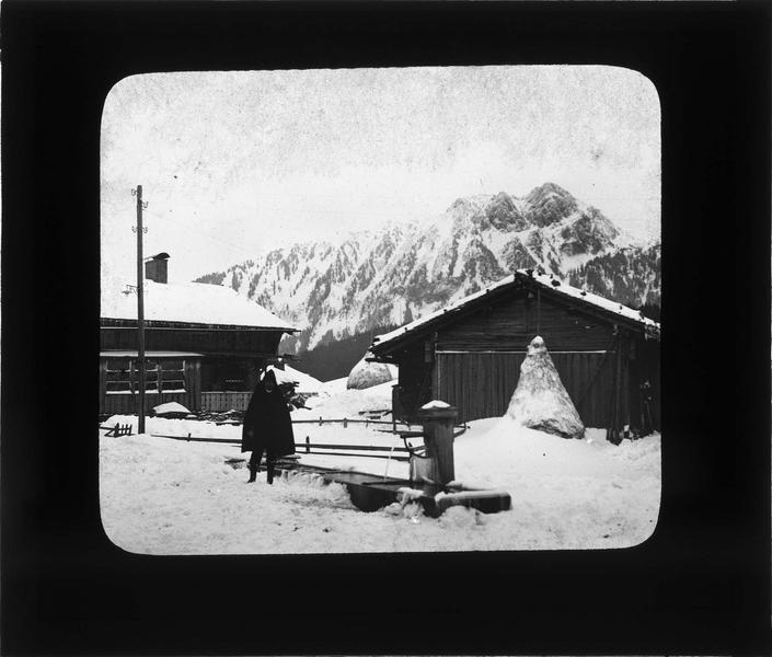 Chalets sous la neige, fontaine avec un homme et Chamossaire en arrière-plan