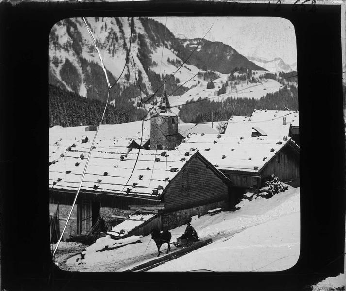 Toits des chalets et clocher de l'église couverts de neige, vue animée avec traineau tiré par un cheval