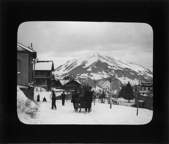Rue sous la neige et Pic Chaussy en arrière-plan, vue animée avec promeneurs et deux hommes tirant un traineau