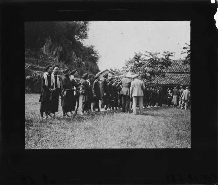 Vietnamiens armés d'arbalètes et de fusils alignés devant des colons
