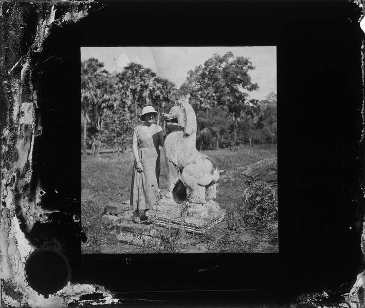 Portrait d'une femme avec chapeau colonial posant à côté d'une statue de lion