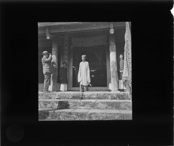 Vietnamiens et homme en tenue coloniale à l'entrée d'une pagode