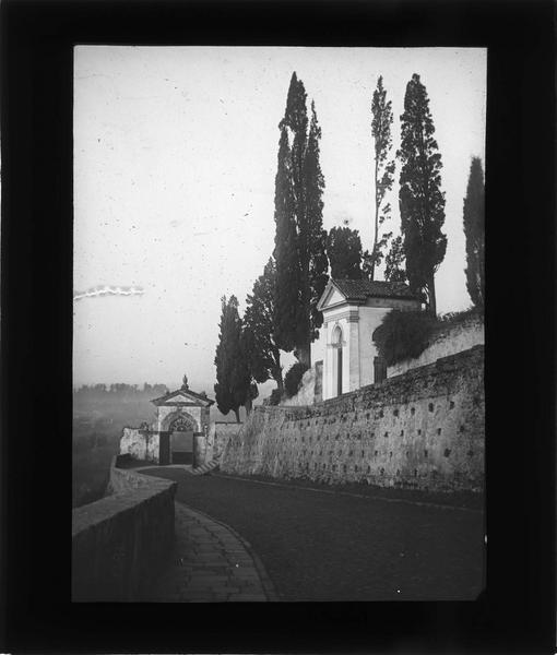 Chemin bordé de chapelles et porte sacrée en arrière-plan
