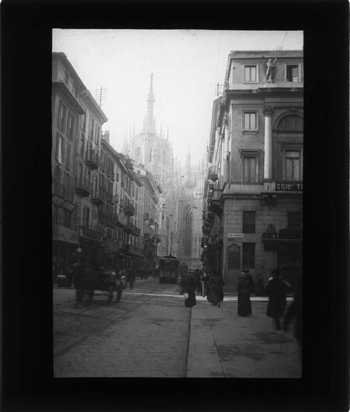 Façades sur rue animée avec tramways et cathédrale en arrière-plan