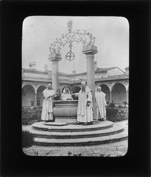 Cloître : puits dans le jardin avec moines
