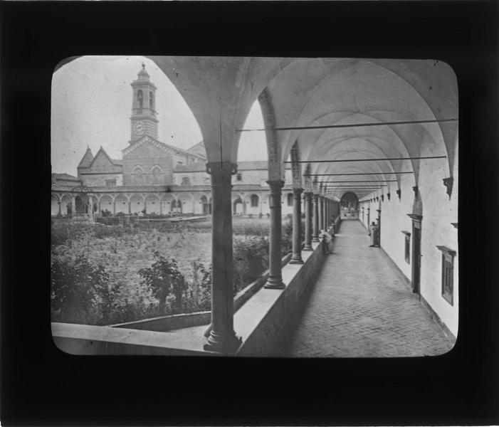 Cloître, intérieur : galerie avec vue sur le jardin et le clocher de l'église de San Lorenzo