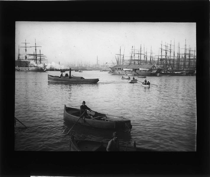 Bateaux amarrés au port, vue animée avec barques au premier plan