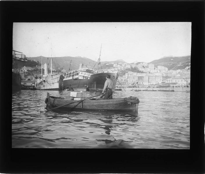 Bateaux amarrés au port, vue animée avec homme debout dans une barque au premier plan