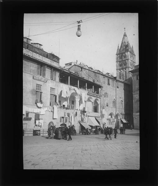 Façades sur rue animée et clocher de la basilique Santa Maria delle Vigne en arrière-plan