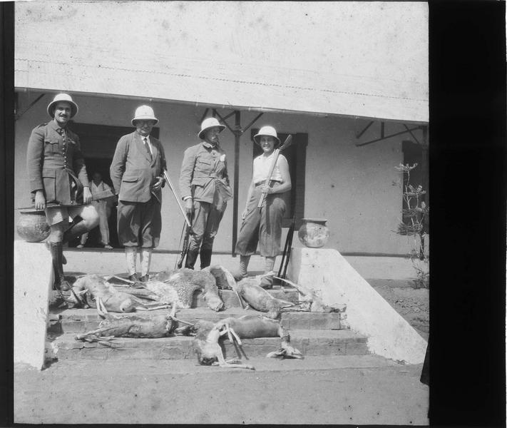 Groupe en tenue coloniale posant devant une maison avec son butin de chasse