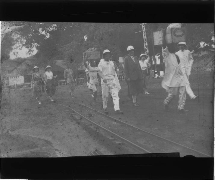 Groupe en tenue coloniale et porteurs dans une rue