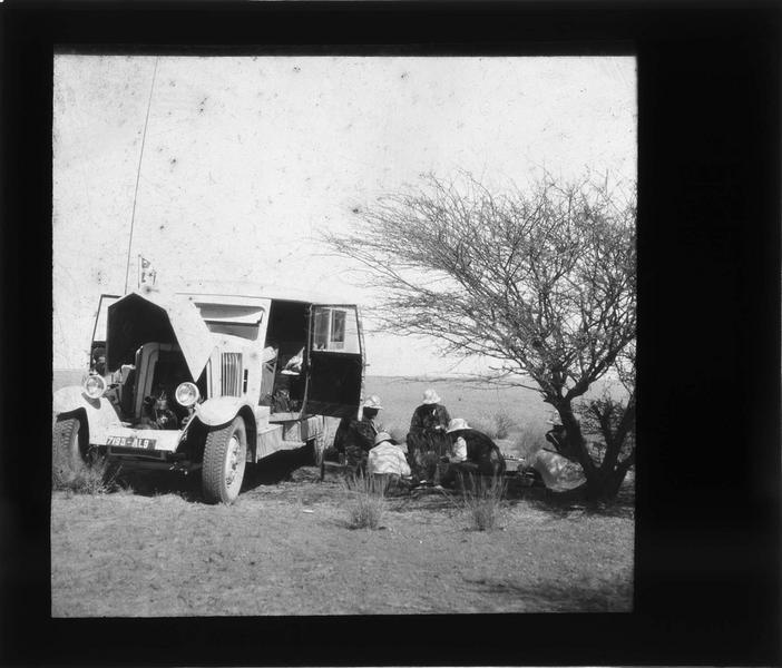 Halte dans le désert, voyageurs à l'ombre d'un arbre à côté d'un véhicule de la Compagnie générale transsaharienne capot ouvert