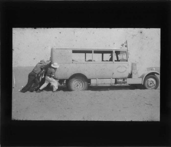 Bidon V: point de ravitaillement de la Compagnie générale transsaharienne; groupe poussant un véhicule de la Compagnie générale transsaharienne ensablé