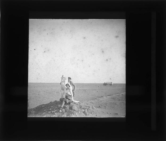 Homme et femme posant à côté d'une balise kilométrique 100 dans le désert du Sahara
