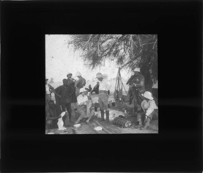 Halte dans le désert, voyageurs et autochtones déjeunant à l'ombre d'un arbre