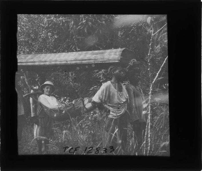 Femme en tenue coloniale portée dans un hamac par des autochtones près de la chute de Ditinn