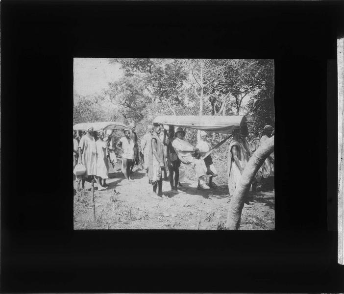 Homme en tenue coloniale porté dans un hamac par des autochtones près de la chute de Ditinn