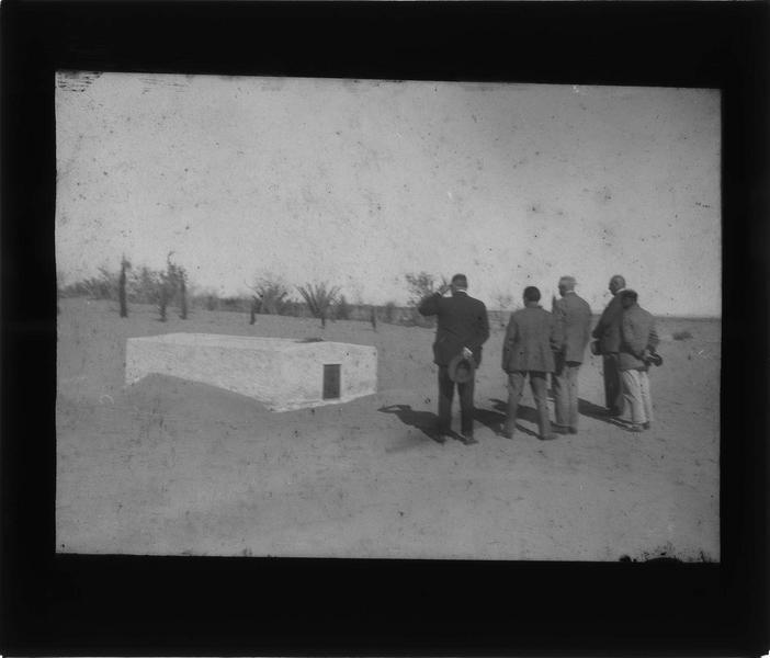 Groupe d'hommes recueillis devant la tombe