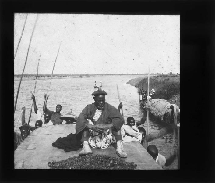 Homme assis sur le toit d'une pirogue et rameurs