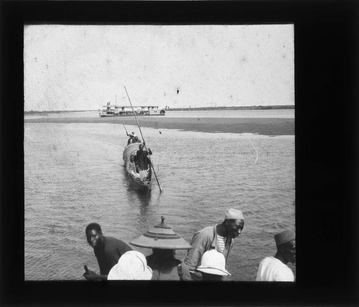 Hommes en pirogues sur le fleuve Niger et le bateau à vapeur 'Mage' au loin